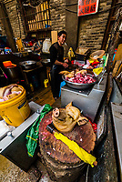 A butcher cutting open a pig's head in the farmer's market, Shangri La (Zhongdian), Yunnan Province, China.