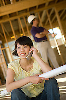 Young woman using mobile phone in construction site