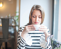 Beautiful young woman drinking coffee in cafe