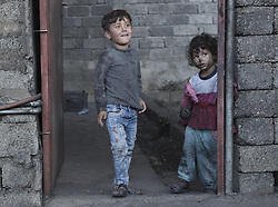 October 21, 2016 - Qayyarah, Iraqi-Kurdistan, Iraq - Two oil covered Iraqi children are seen in a neighbourhood of Qayyarah, Iraq, where several oil wells are currently ablaze. The wells, located in a residential area on the edge of the town, are part of a large oilfield set alight in July by retreating Islamic State militants as part of a scorched earth policy...Since being retaken from the Islamic State the town of Qayyarah has become an important staging post for the Iraqi Army, and some US support elements, in the buildup to the Mosul offensive. (Credit Image: © Matt Cetti-Roberts/London News Pictures via ZUMA Wire)