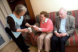 Carer bringing a cup of tea to older couple,