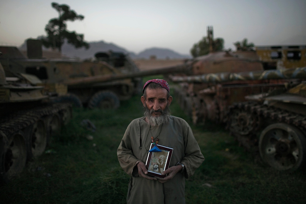 Afghan Mohammad Akbar, 65, a former Mujahedeen fighter who became blind of his right eye, asks for a portrait holding his picture when he was 30, after cutting some grass near Soviet tanks destroyed during the 80's war, in Kandahar, Afghanistan, on May 9, 2011. Photo by Mauricio Lima for The New York Times