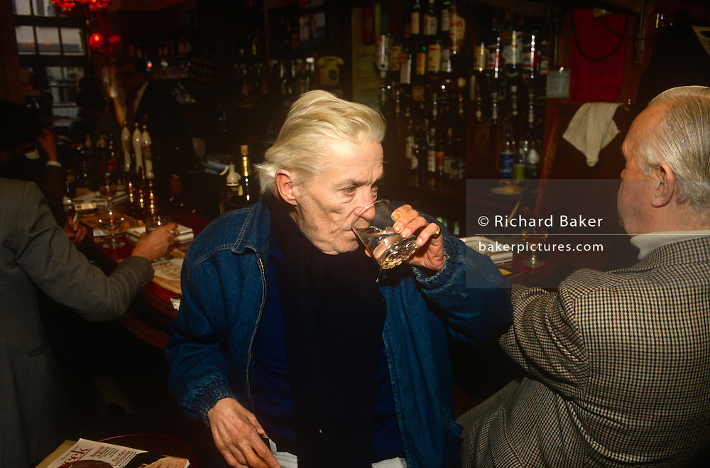 "English writer, Jeffrey Barnard drinks at lunchtime in his favoured Coach And Horses pub, in the summer of 1990 in Soho, London, England. Jeffrey Bernard (1932 – 1997) was a British journalist, best known for his weekly column ""Low Life"" in The Spectator magazine, and also notorious for a feckless and chaotic career and life of alcohol abuse. He became associated with the louche and bohemian atmosphere that existed in London's Soho district. He was later immortalised in the comical play Jeffrey Bernard Is Unwell by Keith Waterhouse."