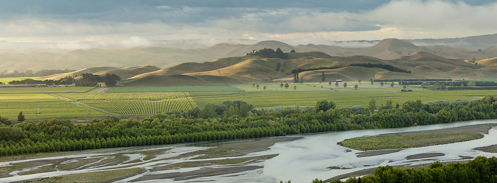 The Ngaruroro river with vineyards in the background. Early morning mist rises from the hills.