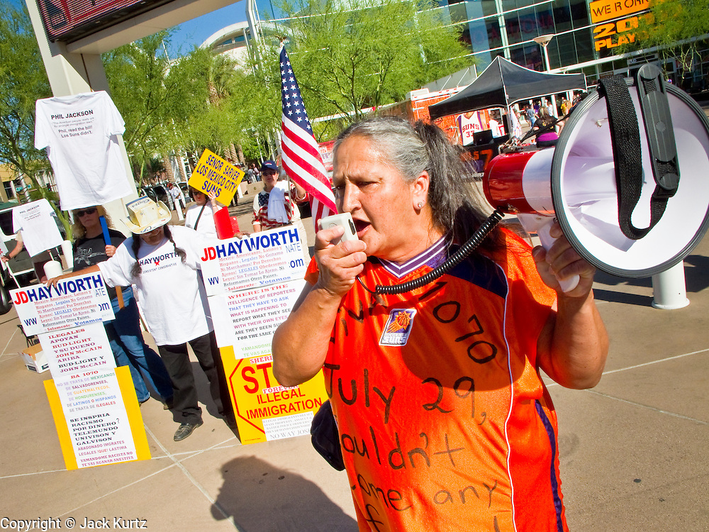"25 MAY 2010 - PHOENIX, AZ: Picketers in front of US Airways Arena in Phoenix, Tuesday, May 25. People opposed to illegal immigration and in favor of Arizona SB1070 picket the Phoenix Suns playoff game against the Los Angeles Lakers Tuesday. About 10 people attended the protest. One person opposed to SB1070 held a counter demonstration. SB1070 makes it an Arizona state crime to be in the US illegally and requires that immigrants carry papers with them at all times and present to law enforcement when asked to. People are picketing the Suns games because Suns owner Robert Sarver has expressed opposition to the law and has had the Suns wearing jerseys that say ""Los Suns.""  PHOTO BY JACK KURTZ"