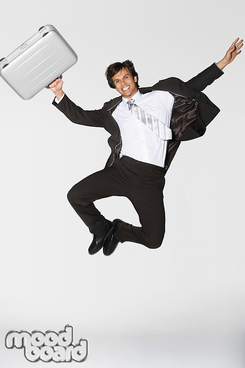 Smiling young businessman holding briefcase jumping clicking heels