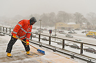 Merrick, New York, U.S. January 21, 2014. Maintenance of Way (MOW) workers for the Metropolitan Transit Authority (MTA) shovel snow as it falls heavily on the windy elevated platform of the Merrick Train Station. The Metropolitan Transit Authority added extra afternoon trains to Long Island Rail Road. Governor Cuomo declared a state of emergency due to the snow storm, with up to 10 inches of snow expected.