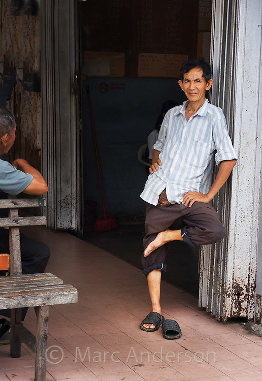 A chinese man standing on one leg and leaning against a wall..
