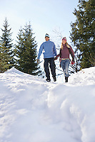 Couple descending snow-covered hill low angle view