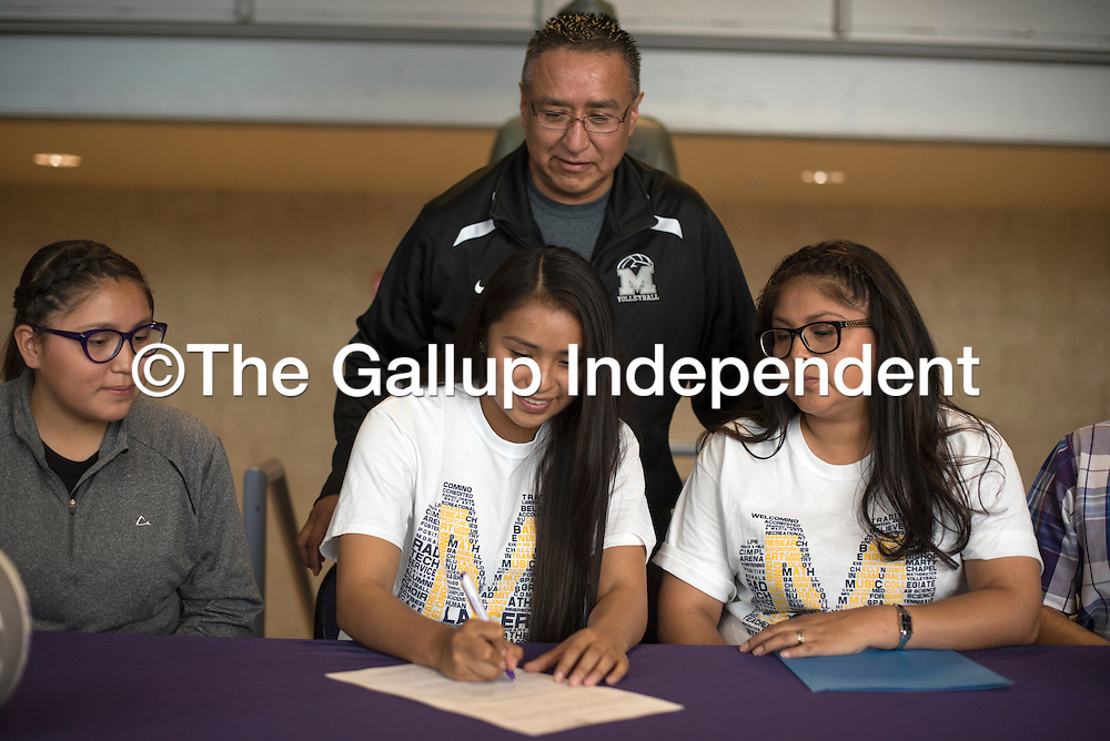 Yael Morgan signs her letter of intent to attend Mount Marty College for volleyball at Miyamura High School in Gallup Thursday.