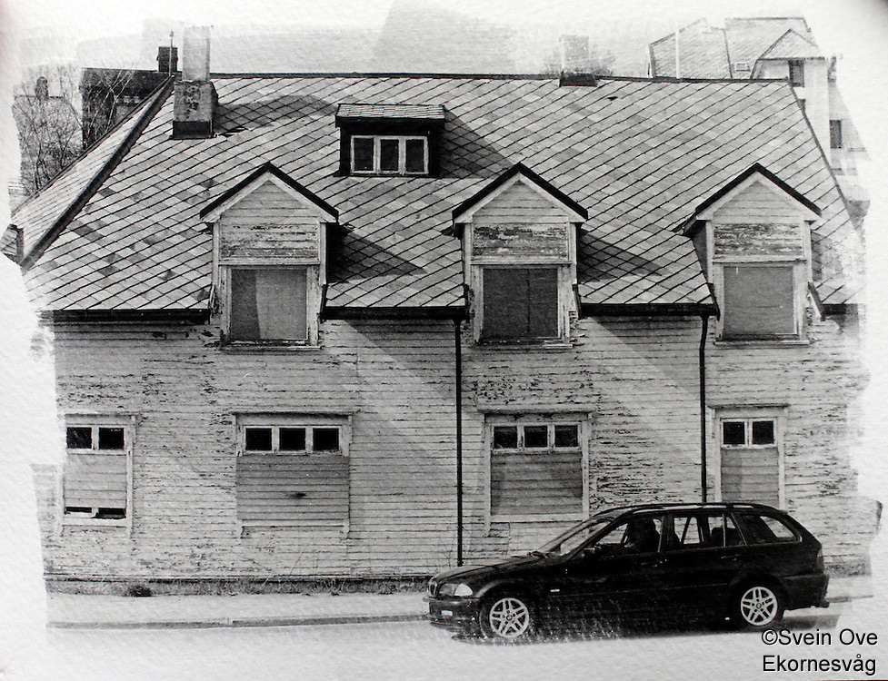 Ålesund 2012. En BMW kjører forbi et gammelt hus i Ålesund som skal rives.