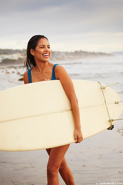 A beautiful young woman holding a surfboard walks out of the ocean surf in San Diego, California.