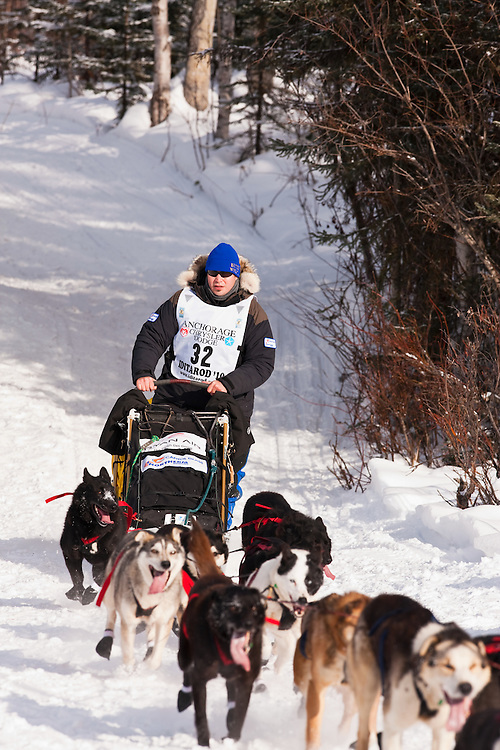 Musher Robert Nelson competing in the 38th Iditarod Trail Sled Dog Race entering Long Lake after leaving the Willow Lake area at the restart in Southcentral Alaska.  Afternoon.