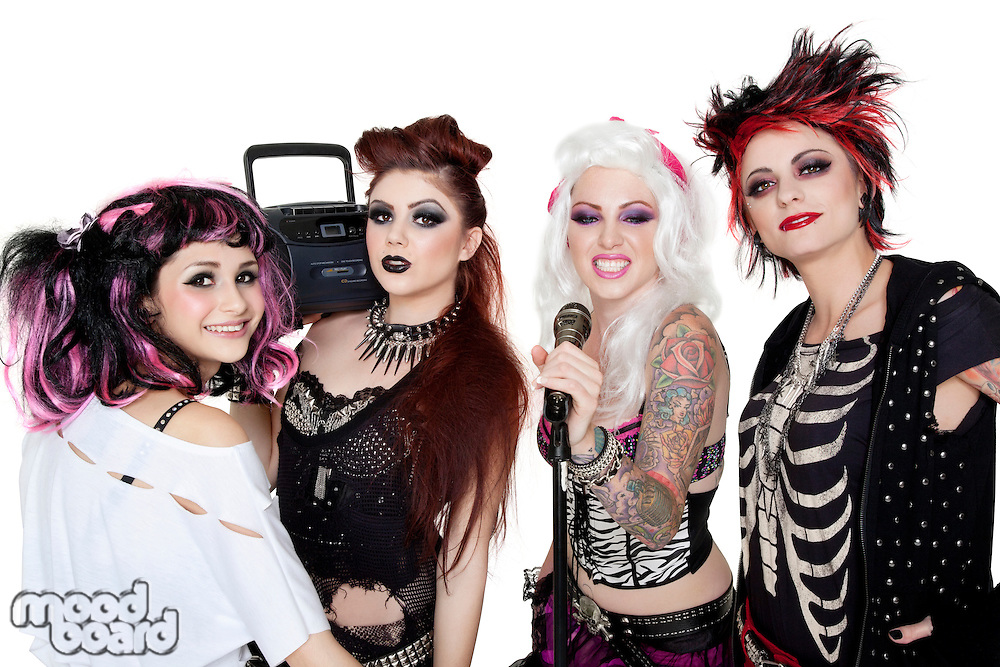 Portrait of all female band with microphone and boom box over white background