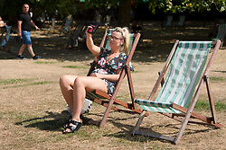 © Licensed to London News Pictures. 07/08/2018. London, UK.  A woman in a deckchair takes a selfie as she sunbathes in London during another day of hot and sunny weather in the capital.  Photo credit: Vickie Flores/LNP