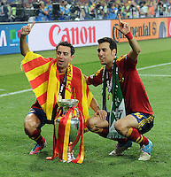 Sergio Busquets and Xavi of Spain pose with the European Championship trophy at full-time