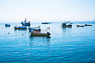 Coquimbo, Chile--April 7, 2018. Small boats at anchor in the Coquimbo harbor in the morning. Foothills of the Andes are in the distance.