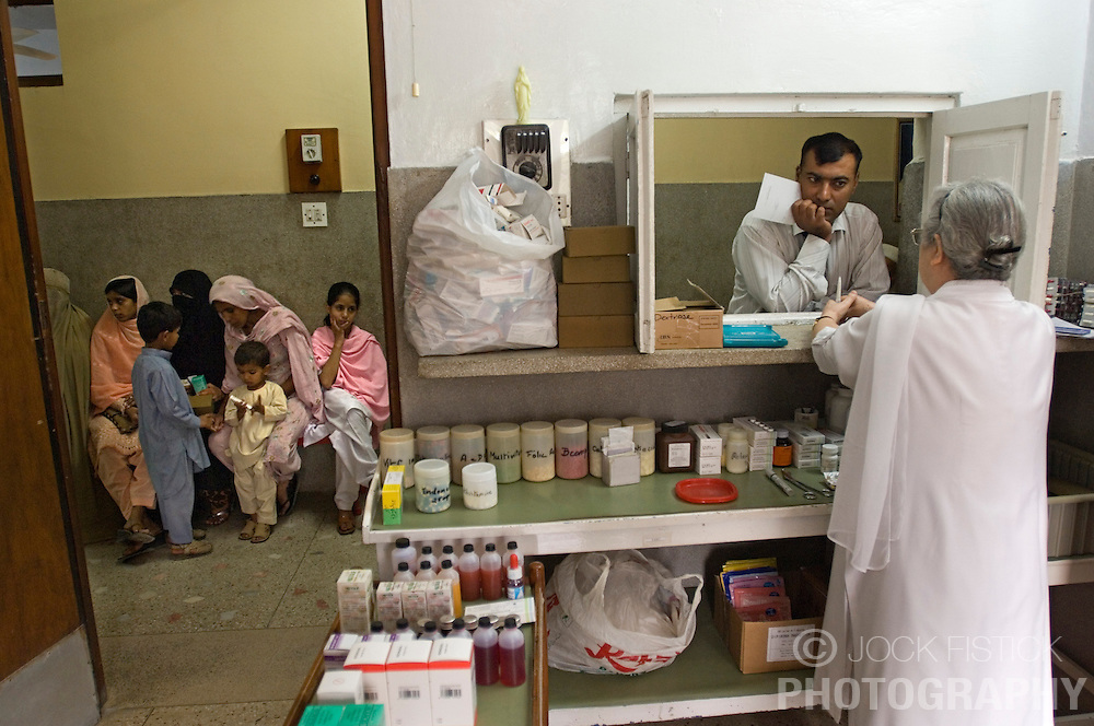RAWALPINDI, PAKISTAN - NOV-01-2006 - Medical staff treat patients at the St. Joseph Hospice day clinic. The hospice was started by Father Francis O'Leary, an Irish missionary, in 1964. Franciscan nuns of the Missionaries of Mary, run the hospice and have a fully trained staff of 26 Pakistani nurses aides and volunteer doctors. The hospice, orphanage and free clinic has 60 beds for resident patients and treats 80-90 out patients daily.  All medical services are free of charge to resident patients at St. Joseph's, regardless of the cost, duration or type of treatment required. The hospice is supported solely by donations.  (PHOTO © JOCK FISTICK)