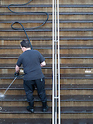 Man cleaning stairs with a water hose at the entrance to the Columbuse Circle subway station early in the morning in Manhattan, New York City.