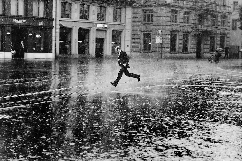 Man running across Paradepatz, the centre of Switzerland's banking industry, during a sudden heavy rain storm.