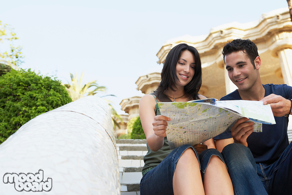 Young couple sitting on stairs reading map portrait