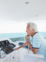 Middle-aged man sitting at helm of yacht side view