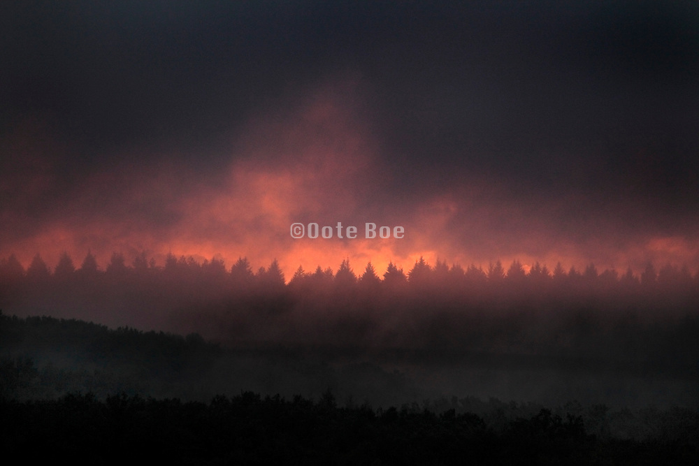 dark setting clouds over wooded rural landscape with tin sliver of sun light