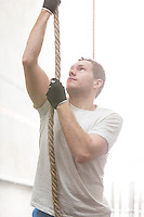 Determined man climbing rope in crossfit gym
