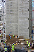 Workmen on a construcion site work beneath the concrete core of a new building being erected in the City of London.