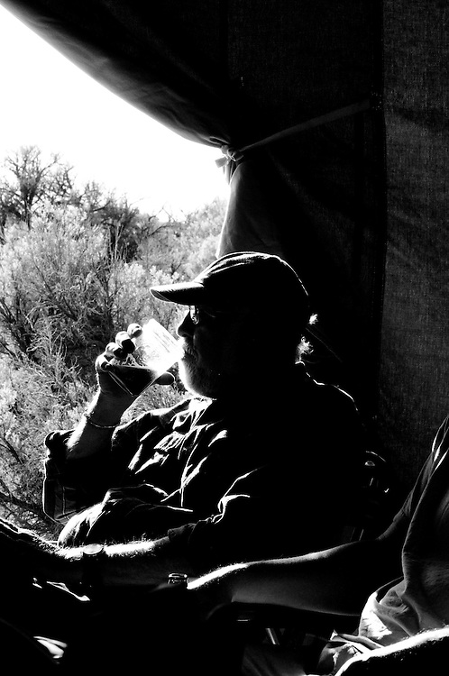 Dr. Steven G Herman enjoying a cool beverage under a wall tent at the Malheur Bird Observatory in central Oregon.