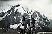 two men standing in panoramic mountain range landscape 1934 France Alps