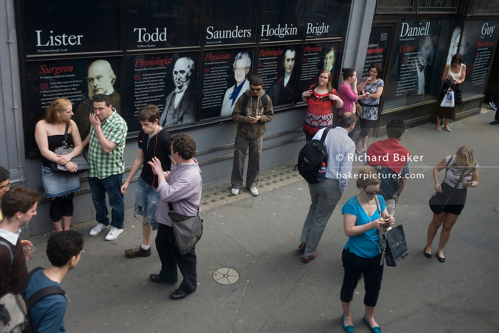 Aerial view of commuters at a city bus stop outside King's College on the Strand, whose alumni faces and names adorn the outside of the London college.