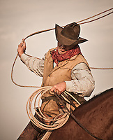 Cowboy prepares to throw the lasso from horseback. Petaluma California, USA.<br />