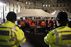 © Licensed to London News Pictures. 31/12/2017. London, UK. Police watch as ticket holders are searched as they enter the secure area to watch the New Year's Eve fireworks at midnight. Photo credit: Peter Macdiarmid/LNP