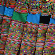 Material for sale at the Lung Khau Nhin Market. Vietnam. Lung Khau Nhin Market is rural tribal market hiding itself amongst the mountains and forests of the far north Vietnam about 10 km from the border with China. The market plays an important role for the local ethnic people, Flower Hmong, Black Zao, Zay, and very small ethnic groups  Pa Zi, Tou Zi, Tou Lao. Tourist trips to the market run from Sapa and Lao Cai every week. Lung Khau Nhin Market, Vietnam.15th March 2012. Photo Tim Clayton