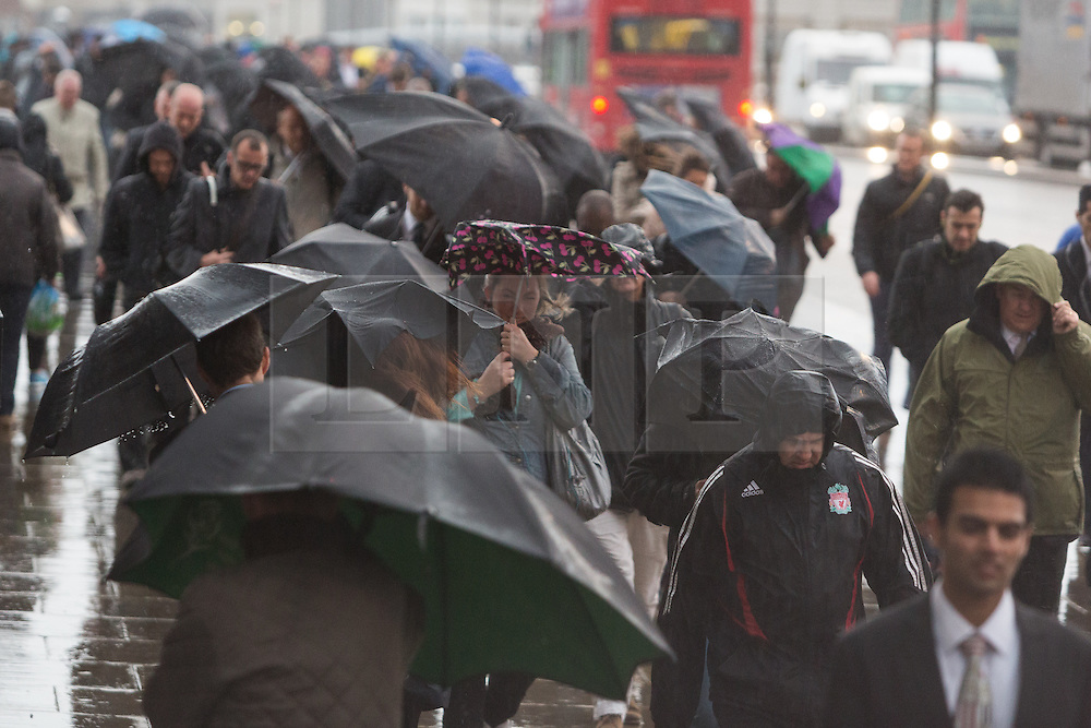 © Licensed to London News Pictures. 21/10/2014. London, UK. Commuters walk to work over London Bridge during heavy rain and wind in the City of London this morning, 21st October 2014 after the end of Hurricane Gonzalo reached the UK overnight. Photo credit : Vickie Flores/LNP