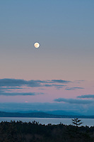 The nearly full moon rises at sunset over the ocean in Victoria, BC
