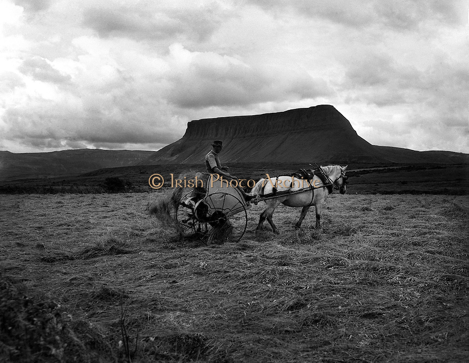 """Views - Ben Bulben, Co. Sligo.25/04/1957..Ben Bulben, sometimes spelt Benbulben or Benbulbin (from the Irish: Binn Ghulbain), is a large rock formation in County Sligo, Ireland. It is part of the Dartry Mountains, an area sometimes called """"Yeats Country""""..Ben Bulben is listed as a protected structure..""""Ben Bulben"""", """"Benbulben"""", and """"Benbulbin"""" are all anglicizations of the Irish name """"Binn Ghulbain"""". """"Binn"""" is the word most often used for """"peak"""" or """"mountain"""", while """"Ghulbain"""" means either """"Gulban('s)"""" or """"jaw-shaped"""". The two most common translations are """"Gulban's peak"""" and """"jaw-shaped peak."""".Ben Bulben was formed during the Ice age, when Ireland was under glaciers. Originally it was a large ridge. The moving glaciers shaped it into its present distinct formation. ."""