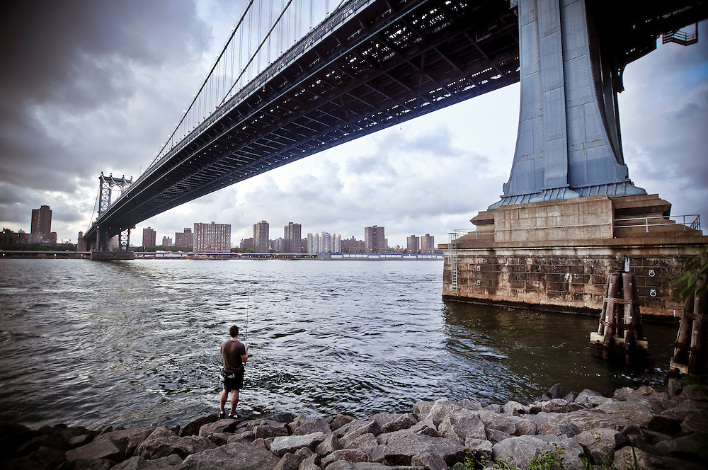 A man fishes by the Manhattan Bridge in DUMBO, Brooklyn, New York.