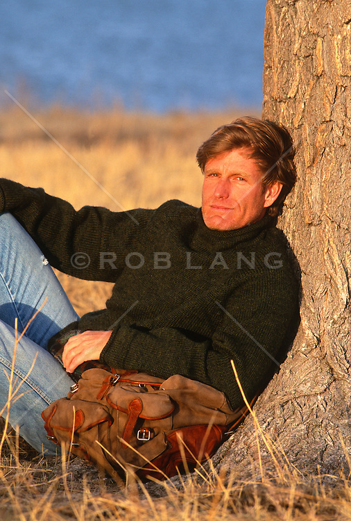 Blond 40 something man resting by a tree during a sunset in New Mexico
