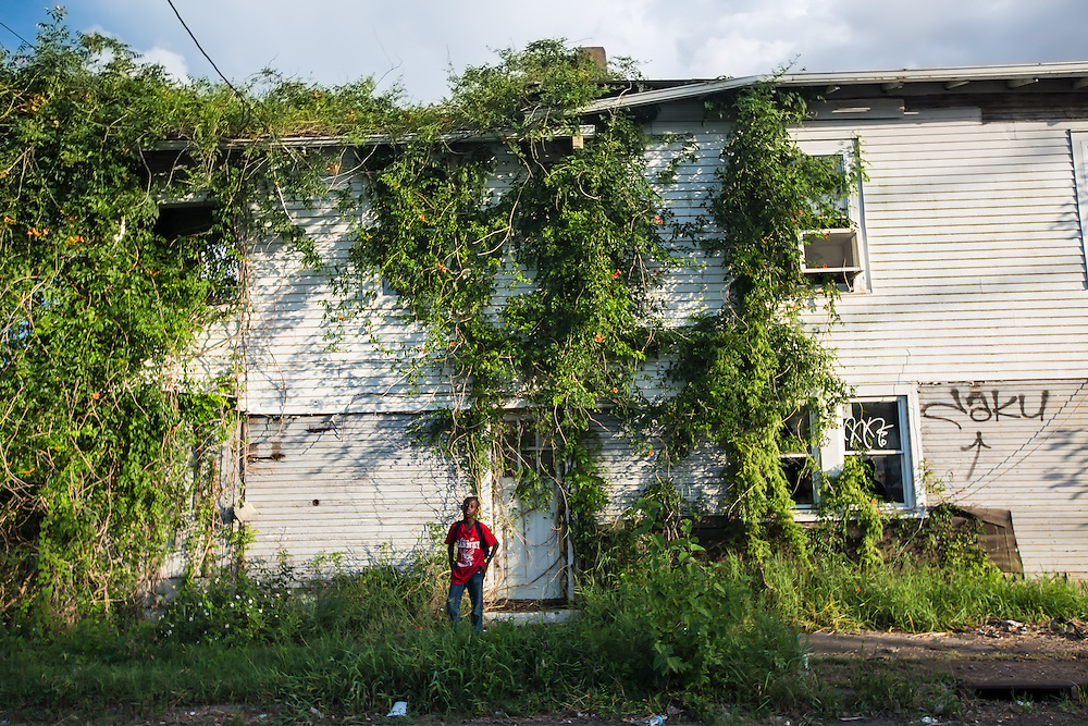 June 11, 2015, New Orleans, LA,  Myron Jones who was 2 years old when Katrina hit poses in front of a blighted home overgrown with vines almost ten years after Hurricane Katriana.