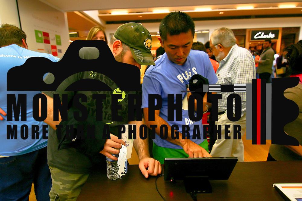 Customers Hiro Takizawa (Right) and Dan Burton review the Samsung series 7 tablet P.C. at the New Microsoft store Saturday, Sept. 29 2012, at Christiana Mall in Newark DE..