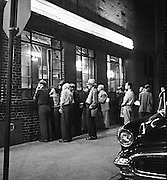 Night photograph of a group of fourteen men gathered to look into windows of a bar or cafe. Greenwich Village, New York. Unusual expressions and setting. Somewhat mysterious  in regard to what was drawing their attention. lamps in bar and neon light beer sign brighten the photograph, large outside light illuminating the entire sidewalk.