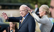 Republican presidential candidate John McCain waves to supporters as his wife Cindy fixes his hair outside United Methodist Church in Phoenix, Arizona, USA where they cast their votes on US Election Day 04 November 2008. McCain is running against Democratic presidential candidate Barack Obama for the office of the 44th President of the United States.