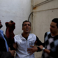 Anti-Mubarak protests in Alexandria. AFRICA, EGYPT, ALEXANDRIA,28.01.2011: after the Friday prayers protesters rally in thousands against the government. Huge numbers of security police forces are on the streets. Soon, the situation turns violent, with the police using tear gas and the demonstrators throwing stones and petrol bombs. These young men are recovering from tear gas attacks in the backyard of a building.