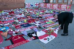 © Licensed to London News Pictures. 30_06_2015. Walsall, West Midlands, UK. The scene at Bescot Stadium, Walsall Football ground earlier today as tributes to Patrick Evans, Adrian Evans and Joel Richards, killed in Tunisia, were laid out. Pictured, a man on his way to work adds his England flag to the many tributes. Photo credit : Dave Warren/LNP
