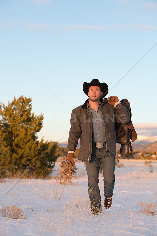 All American cowboy with a saddle on top of a mountain range in the snow