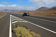 Chevron road lines on main highway through Malpaís Grande national park, Fuerteventura, Canary Islands, Spain