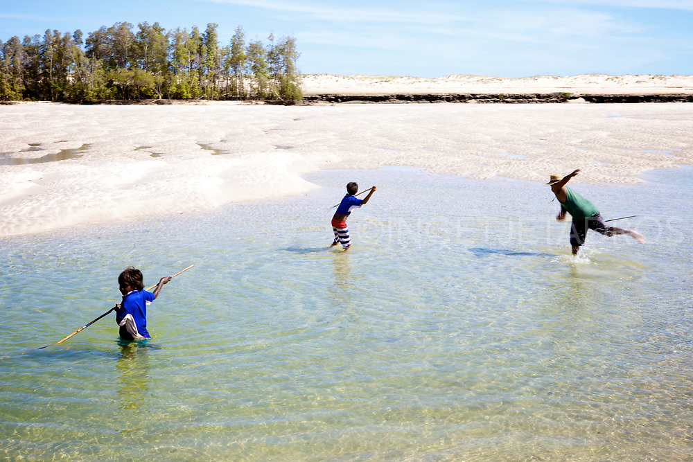 Aboriginal boys spearing for crab, they made their own spears. Aboriginal people in One Arm Point hunt on dugon and turtle, while fishing, and mud crabbing is a part of daily life. The Dampier Peninsula is a peninsula located north of Broome and Roebuck Bay in Western Australia.  One Arm Point a remote Aboriginal community which is a 2 hour drive north of Broome on the Cape Leveque Road. <br />