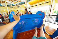Nunley's Carousel, with person's legs and arm flung out, riding a coach or bench seat, in Museum Rose, Garden City, New York, USA, 2012